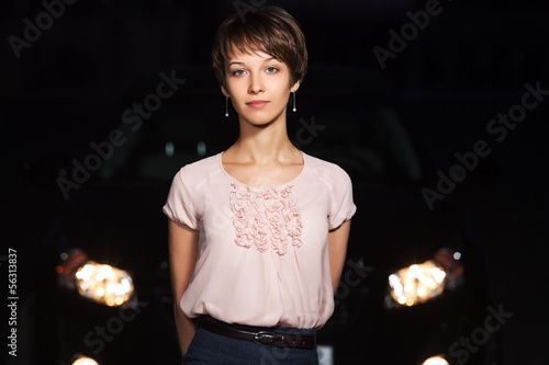 Young woman in the night in front of car headlights