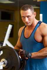 Strong man preparing his training machine in fitness