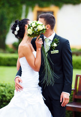 Couple just married  kissing behind bouqet