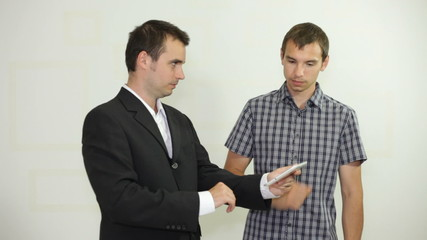 Two businessmen looking at digital tablet