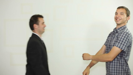 Two funny businessmen handshaking and jumping