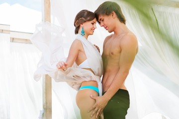 Sexy young couple standing under summer awning