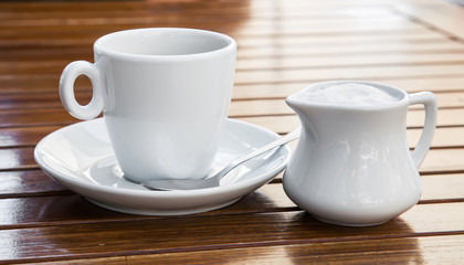 Cup of coffee and milk jug on the table