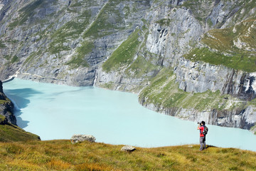 photographer and a lake in the Swiss Alps