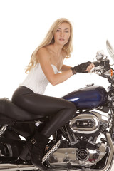woman white top black pants sit motorcycle looking