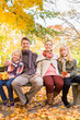 Happy Family outdoors sitting on bench in autumn