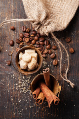 Cinnamon sticks, cane sugar and coffee beans on wooden backgroun