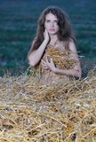 The seminude girl is covered with hay