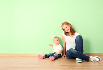 happy family of mother and child sitting on the floor in an empt