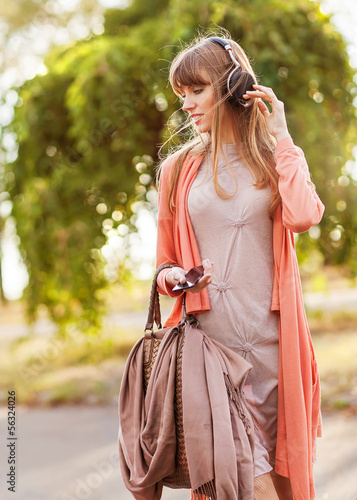 Young beautiful girl listening to MP3 player