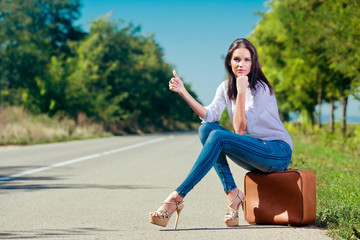 Beautiful woman hitchhiking with suitcase