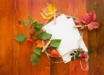 Autumn leaves with white paper for text.