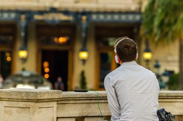 Ragazzo in camicia bianca ascolta musica davanti al casinò