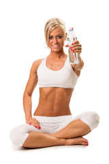 Fit a smiling blond woman holding a mineral water