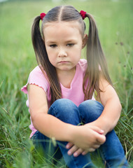 Sad little girl is sitting on green grass