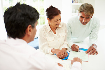 Senior Indian Couple Meeting With Financial Advisor At Home