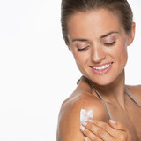 Happy woman applying creme on shoulder