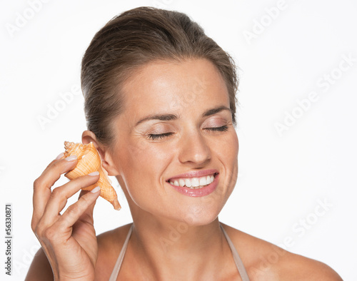 Happy woman hearing waves in sea shell