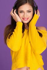 Smiling woman listening music through her headphone