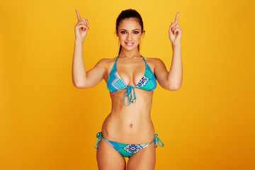 Looking up woman wearing two piece bikini pointing up her hands