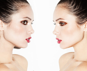 studio portrait of two young beautiful women twins
