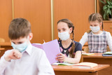 schoolchildren with protection mask against flu virus at lesson