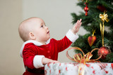 pretty child with gift at Christmas tree