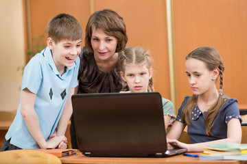 school kids and teacher using laptop at lesson