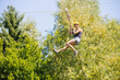 Happy Woman Hanging On Zip Line In Forest