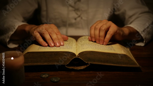 medieval looking man is reading a old book and lifts thumb up