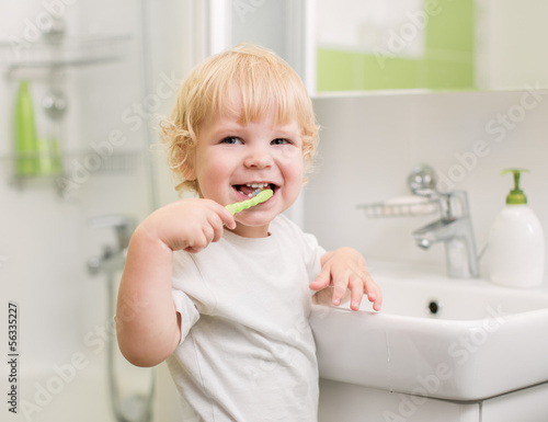 Happy kid brushing teeth