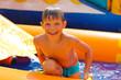Smiling boy in the water near waterslide.