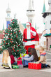 Santa Claus With Children Opening Presents By Christmas Tree