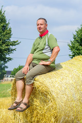 Farmer sitting on straw bales