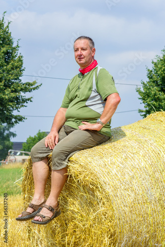 Farmer sitting on straw bales