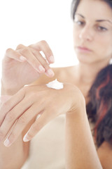 Young woman applies cream on her hands