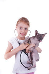 Girl playing a veterinarian with cat shpinx