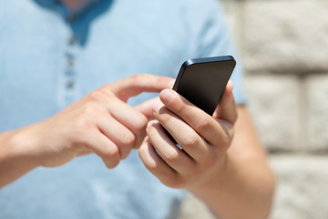 boy holding a phone and a touch screen for finger against a wall