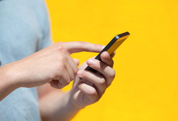 boy holding a phone and a touch screen against a yellow wall