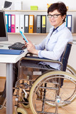 Disabled woman in wheelchair at desk