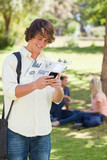 Cheerful student working on his digital smartphone