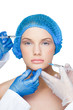 Surgeons making injection on content blonde wearing blue surgica