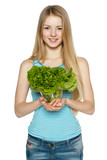 Smiling woman holding lettuce leaves in transparent bowl