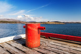 Red mooring bollard on wooden pier in Norway