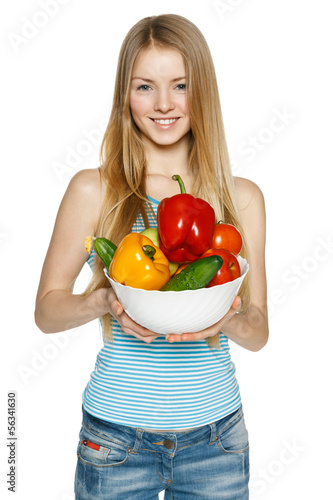 Smiling girl holding bowl with vegetables