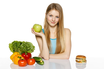 Woman choosing between healthy food and fast food