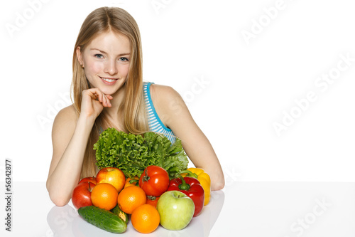 Smiling young woman sitting at the table with vegetables