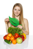 Woman sitting at table with vegetable, showing leaf symbol