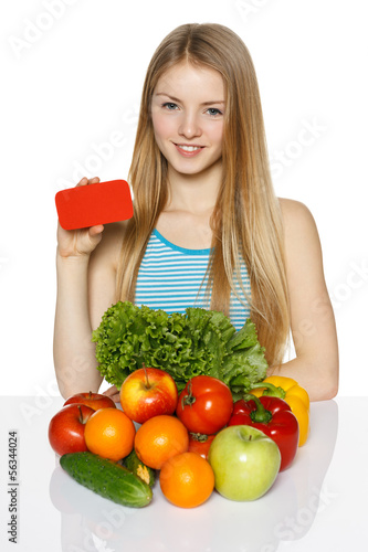 Female with fruits and vegetables holding blank credit card