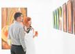 people looking at art gallery paintings